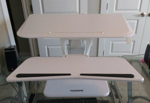 flexispot sit stand desk riser on glass desk in standing position from front with keyboard tray attached