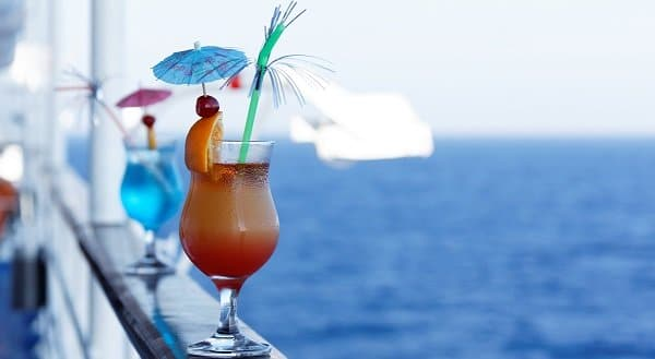 orange and blue cocktails on a cruise ship railing overlooking the water