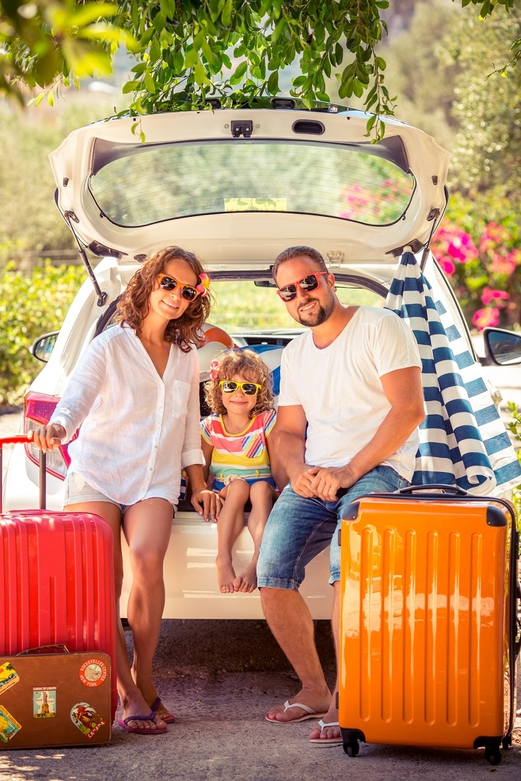 a family mother father and daughter with red and orange suitcases packing their white car for vacation