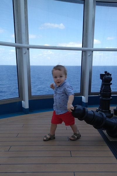 1 year old running on cruise deck carry giant chess piece overlooking water