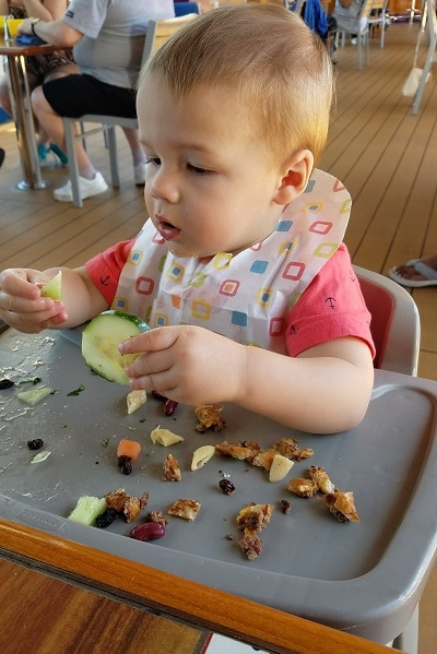 1 year old sitting in high chair eating food on carnival dream cruise ship
