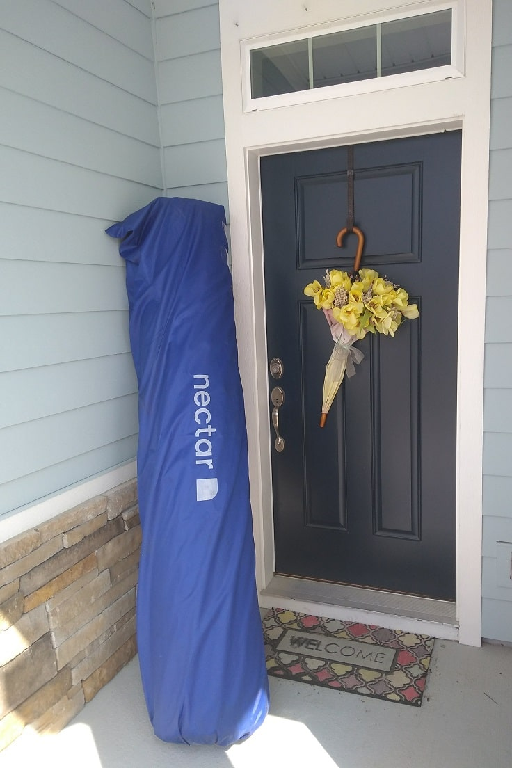 king size nectar mattress rolled in shipping packaging on front porch next to navy blue front door