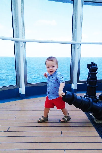 one year old running on cruise ship deck overlooking water holding giant chess piece