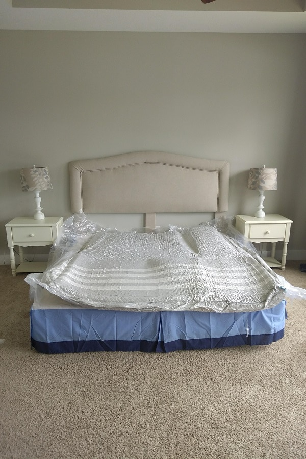 king size leesa mattress shrink wrapped on box springs with beige headboard and two night stands