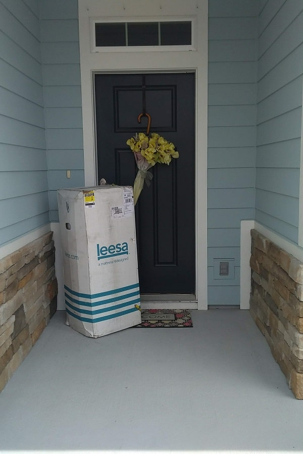 leesa mattress in a leesa box on front porch with stone in front of a navy blue front door