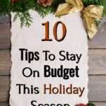 10 tips to stay on budget this holiday season on paper sitting on wood background surrounded with Christmas floral decorations