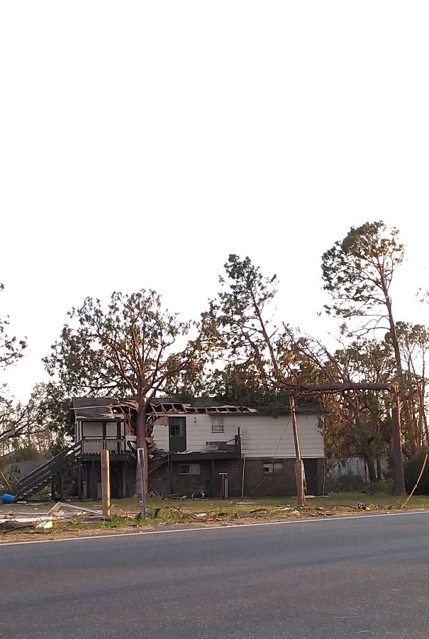 a two story home with a large pine tree that has fallen on and divided the home after Hurricane Michael
