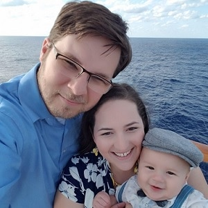 father, mother and son taking selfie picture on cruise ship overlooking water